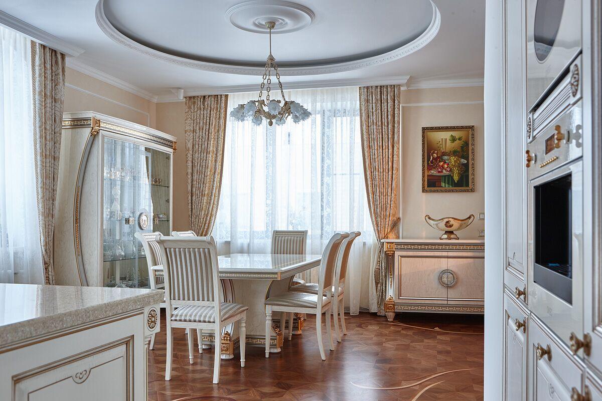 На полу столовой зоны кухни мы видим художественный паркет, который плавно перетекает из гостиной.
