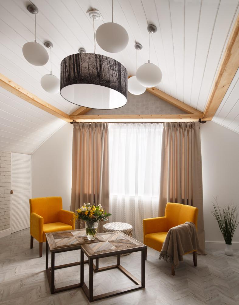 При этом удалось максимально использовать пространство под скосами крыши, а центр комнаты оставить более свободным, для отдыха и застолья.