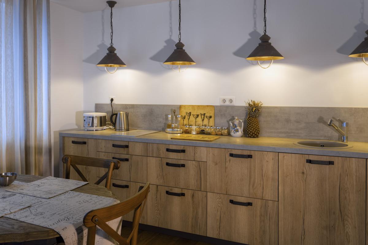 Основная линия кухни не имеет навесных шкафчиков, только нижний ряд, над которым висят металлические светильники.