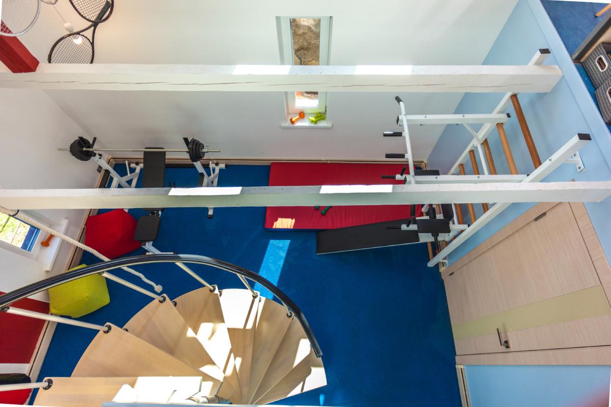 Винтовая лестница вниз ведет на первый этаж в спортзал. Из спортзала дверь в сауну и в столовую - гостиную с камином.