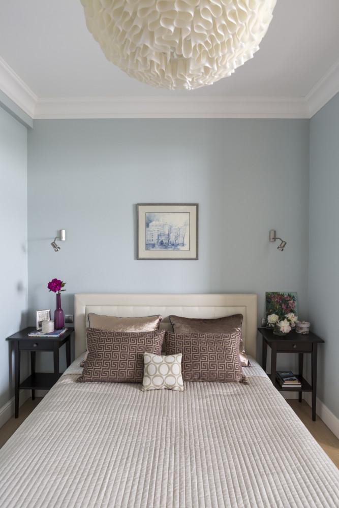 Лёгкая холодная колористическая гамма серо-голубых стен, светлое изголовье кровати, тёмные тумбочки — всё просто.