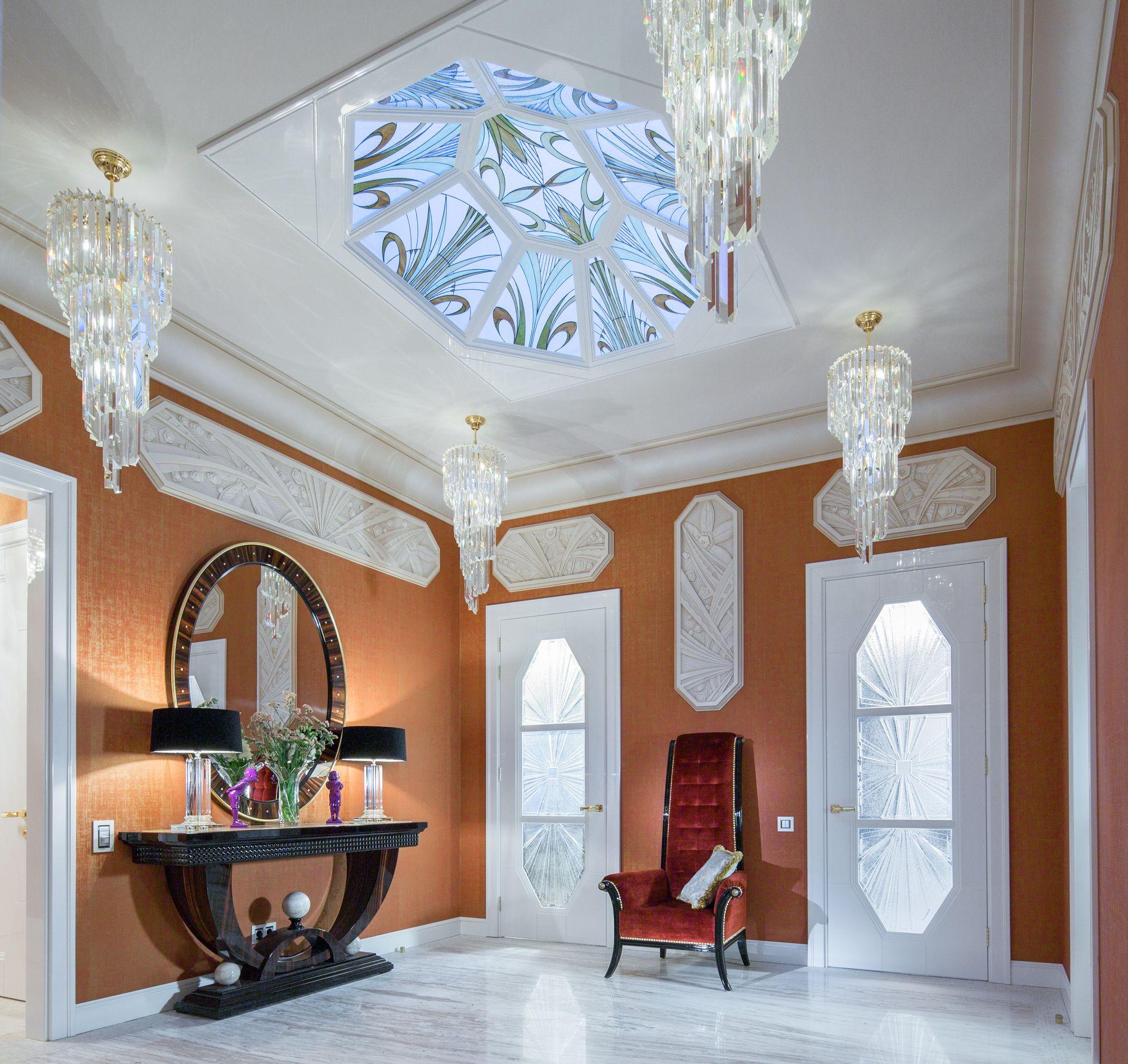 Сразу от входа вы попадаете в сказочный мир Карика и Вали. Световой потолок в прихожей — это огромный лист с прожилками, который сразу задаёт тему для общих пространств. Стена коридора, ведущего через гостиную, декорирована рельефом с изображением огромных цветов-бутонов, среди которых мирно плавают рыбки в аквариуме.