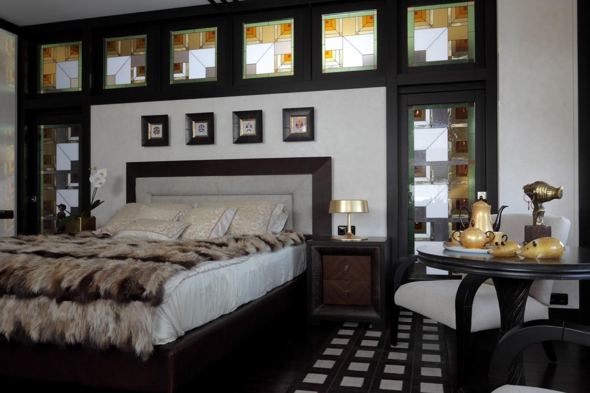 Крокодиловое изголовье кровати перекликается с декором прикроватных тумбочек и сложным рисунком напольного ковра, но более всего гармонирует с покрывалом из лисьих шкур.