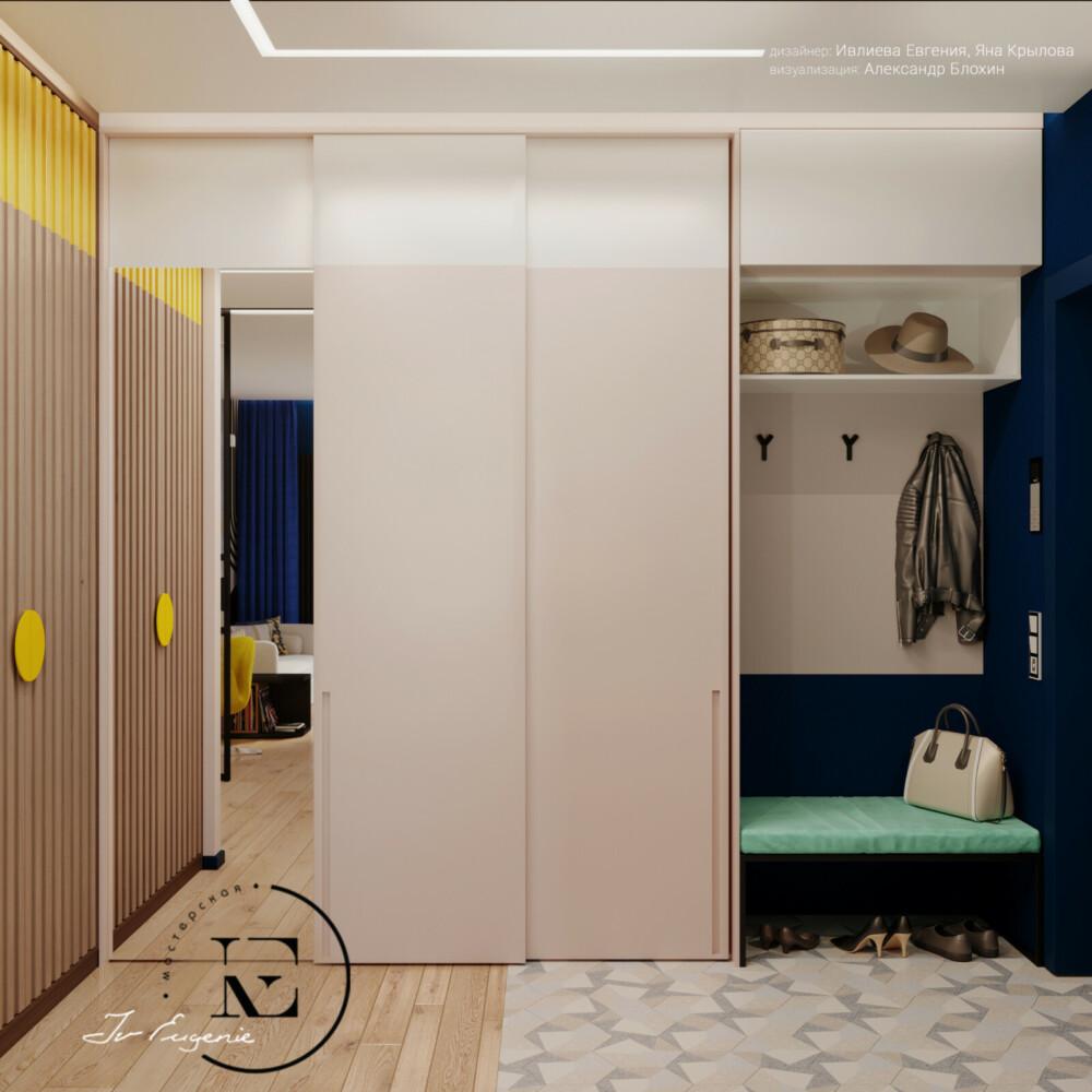 Как грамотно обустроить небольшую прихожую. В нашем проекте два встроенных шкафа и открытая вешалка хорошо «соседствуют» друг с другом. Трехдверный шкаф с белым фасадом и большим зеркалом плавно переходит в небольшую вешалку для верхней одежды.  Мягкая банкетка мятного цвета хорошо сочетается с темно-синей стеной во входной зоне. Узкий шкаф с филенчатыми дверцами и ярким фасадом задает настроение всему помещению.